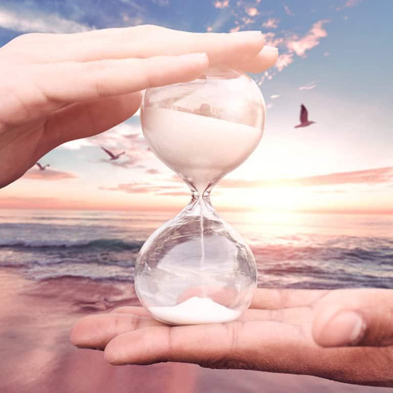 un sablier tenu pas 2 mains sur une plage